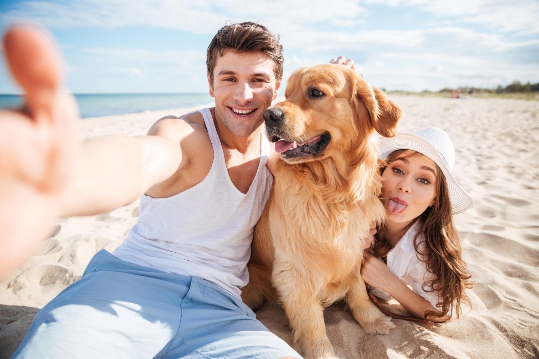 Hund mit Besitzern am Strand